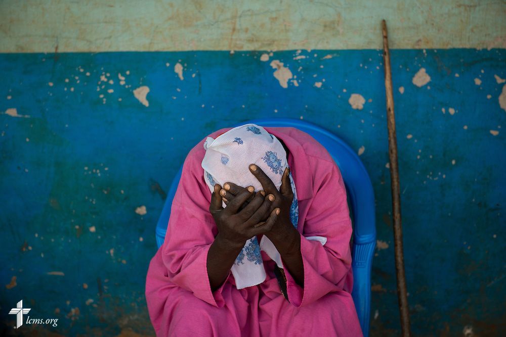 An elderly woman cups her head in her hands from pain as she sits during the Mercy Medical Team clinic Thursday, June 12, 2014, at the Luanda Doho Primary School in Kakmega County, Kenya. LCMS Communications/Erik M. Lunsford