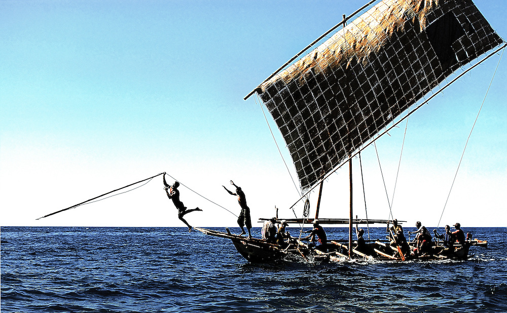 A harpoonist launches himself from the traditional whaling boats bowsprit during a hunt on Lembata Island, Indonesia.
