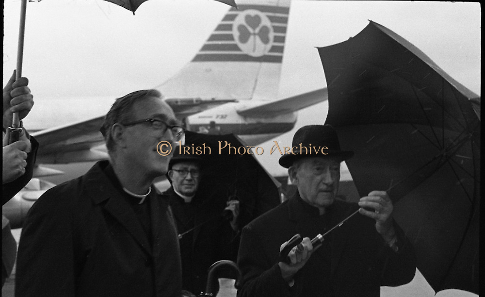 Archbishop Ryan Returns From Rome..1972..16.02.1972..02.16.1972..16th February 1972..After his official appointment as Archbishop of Dublin by Pope Paul VI, Dr Dermot Ryan returned to Dublin for his installation as Archbishop on Feb 22nd at the Pro Cathedral,Dublin..Image of Dr Dermot Ryan Archbishop Of Dublin being protected from the inclement weather on his arrival back in Dublin from Rome.