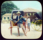 Two rickshaw drivers with their vehicles: Japan, 1895. Hand-coloured lantern slide.
