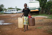 A child carries empty containers in the suburb of Budiriro outside of Harare queue to collect clean water in containers brought to collection points where water bowsers have been supplied by NGO's such as UNICEF. ..