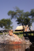young boy jumping into lake off of dock with barn in background enjoying his summer break..Model Released