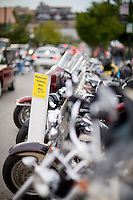 Motorcycles parked side by side on the street during a Motorcycle Rally.