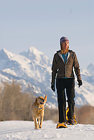 A young woman snowshoes with her dog in Jackson Hole, Wyoming.