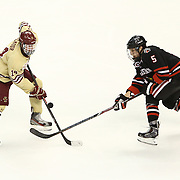 Matt Benning #5 of the Northeastern Huskies and Adam Gilmour #14 of the Boston College Eagles fight for the puck during The Beanpot Championship Game at TD Garden on February 10, 2014 in Boston, Massachusetts. (Photo by Elan Kawesch)