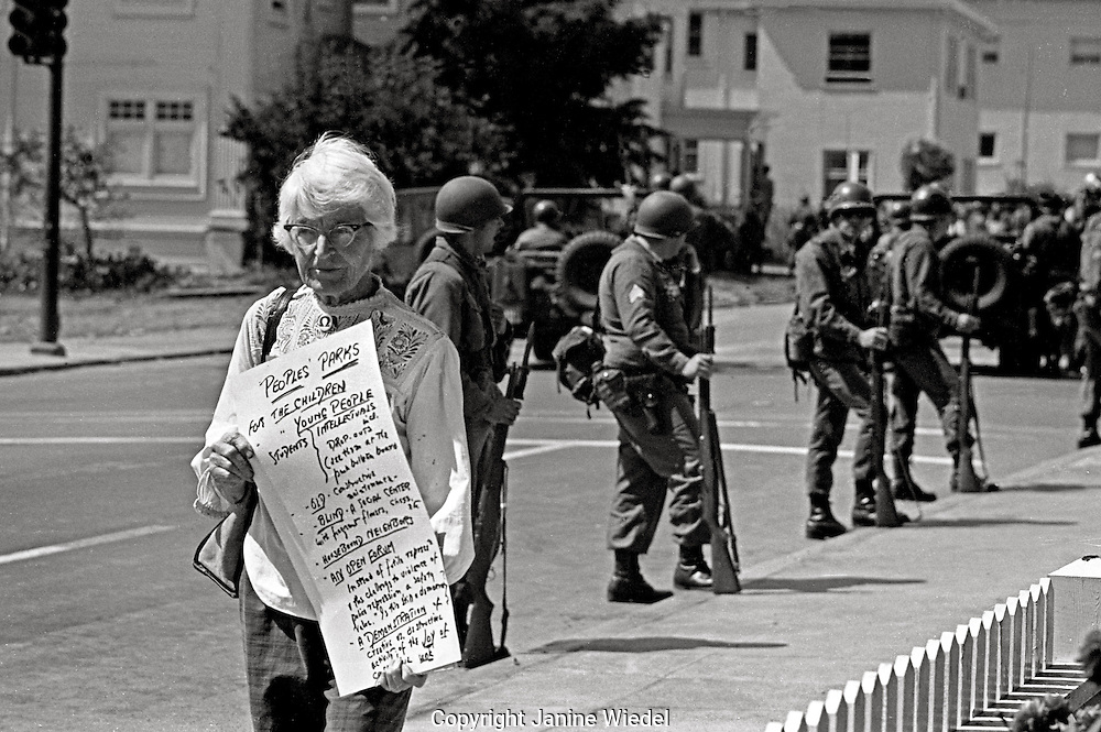 Woman carrying poster with Peoples Park aims protesting while as US National guard troops take over town during People's Park Student protest & riots in Berkeley California 1969