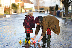 © Licensed to London News Pictures. Date 9 Jan 2014. Oxford. Janie Hampton and her grand daughter Delilah Hampton play with boats in the street. River Thames floods at Oxford causing the closure of the Abingdon and Botley roads.. Photo credit : MarkHemsworth/LNP