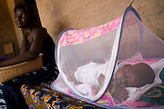 A baby sleeps under a mosquito net in his family's home in the village of Essaout, Senegal, on Thursday June 14, 2007...