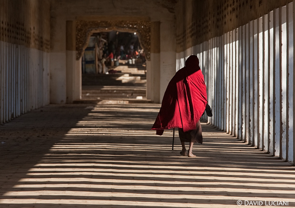A monk passing through a hallway in Bagan.