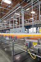 Orange juice bottles on conveyor in bottling plant