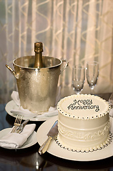"Cake decorated with ""Happy Anniversary"" on a table with Champagne bucket, two champagne flutes, Champagne bottle and silverware"