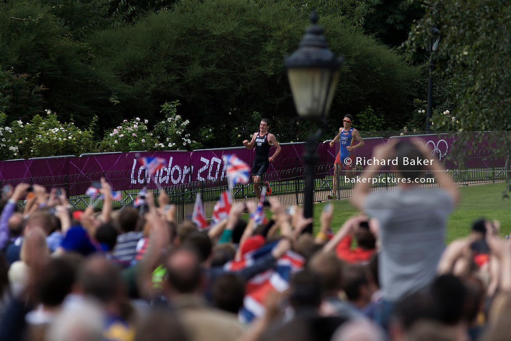 Cheered on by an ecstatic home crowd, Triathletes Team GB Alistair Brownlee followed by Spain's Javier Gomez run through London's Hyde Park on the last lap for the Mens' Triathlon competition in Hyde Park during the London 2012 Olympics, the 30th Olympiad. The Triathlon competitors raced over a 1.5km swim, a 43km bike race and a 10km run - eventually won by Team GB's Alistair Brownlee, Spain's Javier Gomez and Jonathan Brownlee (brother of the winner). The venue was the Hyde Park 142 hectares (350 acres) Hyde Park in the heart of the capital, one of the largest parks in central London and the site of the Victorian Great Exhibition of 1851.