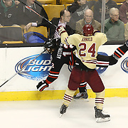 Bill Arnold #24 of the Boston College Eagles pushes Zach Aston-Reese #12 of the Northeastern Huskies into the boards during The Beanpot Championship Game at TD Garden on February 10, 2014 in Boston, Massachusetts. (Photo by Elan Kawesch)