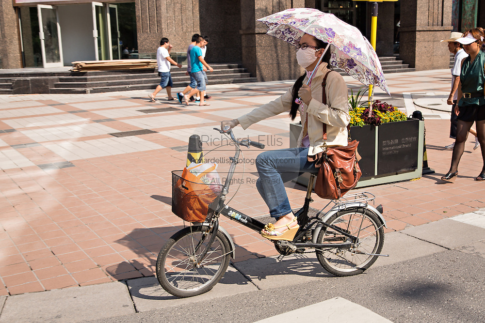 A Chinese woman rides a bicycle with an umbrella and face mask during summer in Beijing, China