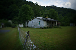 An home sits abandoned in Lindytown, West Virginia. Lindytown was once home to dozens of families, many with roots dating back generations. In 2008, residents started moving away because of a nearby mine. Today, only one original family remains: Quinnie Richmond and her son, Roger. Mountaintop Removal is a method of surface mining that literally removes the tops of mountains to get to the coal seams beneath. It is the most profitable mining technique available because it is performed quickly, cheaply and comes with hefty economic benefits for the mining companies, most of which are located out of state. It is the most profitable mining technique available because it is performed quickly, cheaply and comes with hefty economic benefits for the mining companies, most of which are located out of state. Many argue that they have brought wage-paying jobs and modern amenities to Appalachia, but others say they have only demolished an estimated 1.4 million acres of forested hills, buried an estimated 2,000 miles of streams, poisoned drinking water, and wiped whole towns from the map. © Ami Vitale
