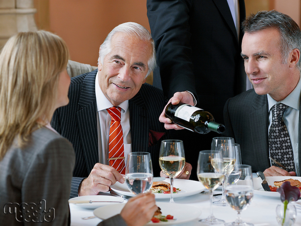 Three business people talking at restaurant table waiter serving wine