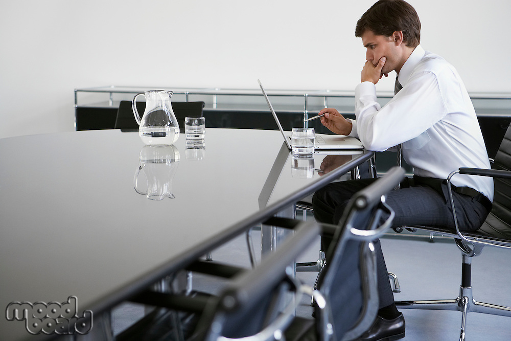 Business man using laptop at conference table