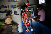Pooja, 14, a student from the village of Pathpuri, Hoshangabad, Madhya Pradesh, India, taking part to the children's journal, a project launched by Dalit Sangh, an NGO which has been working for the uplift of scheduled castes for the past 22 years, is serving tea to her brothers, Jitendra Kumar, 11 (right) and Narendra Kumar, 9. Dalit Sangh is working in collaboration with Unicef India to promote education and awareness within backward communities.
