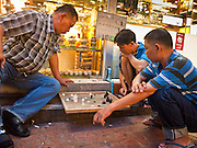 05 JULY 2011 - BANGKOK, THAILAND:   Thai men play checkers on Soi Arab in Bangkok. Soi Arab is an alleyway in Bangkok. What started as an alley has now grown into a neighborhood that encompasses several blocks of restaurants, hotels and money exchanges that cater to Middle Eastern visitors to Thailand. The official name of the street is Sukhumvit Soi 3/1, located in North Nana between Sukhumvit Soi 3 and Sukhumvit Soi 5, not far from the Nana Plaza night-life area and the Grace Hotel popular among Arabs.   PHOTO BY JACK KURTZ