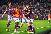 The Hearts players mob Aidan Keena (#35) of Heart of Midlothian FC after he scores the winning penalty during the penalty shoot out at the end of Betfred Scottish Football League Cup quarter final match between Heart of Midlothian FC and Aberdeen FC at Tynecastle Stadium, Edinburgh, Scotland on 25 September 2019.