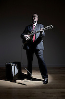 Man in full suit playing electric guitar