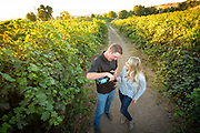 Man pouring wine for woman while couple enjoys walking through the vineyard at Holeinsky Winery in Buhl, Idaho.