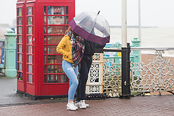 © Licensed to London News Pictures. 31/12/2017. Brighton, UK. Members of the public shelter from the rain as Brighton and Hove is hit by windy and wet weather on 2017 New years eve. Photo credit: Hugo Michiels/LNP