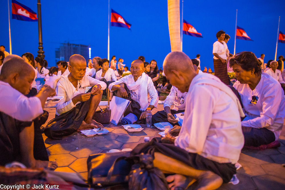 02 FEBRUARY 2013 - PHNOM PENH, CAMBODIA: Cambodian women share a meal on the sidewalk along Sisowath Quay, Phnom Penh's riverfront boulevard, after a prayer service for late Cambodian King Norodom Sihanouk. Much of Phnom Penh has been shut down to honor former King Norodom Sihanouk, who ruled Cambodia from independence in 1953 until he was overthrown by a military coup in 1970. Only bars, restaurants and hotels that cater to foreign tourists are supposed to be open. The only music being played publicly is classical Khmer music. Sihanouk died in Beijing, China, in October 2012 and will be cremated during a state funeral royal ceremony on Monday, Feb. 4.     PHOTO BY JACK KURTZ