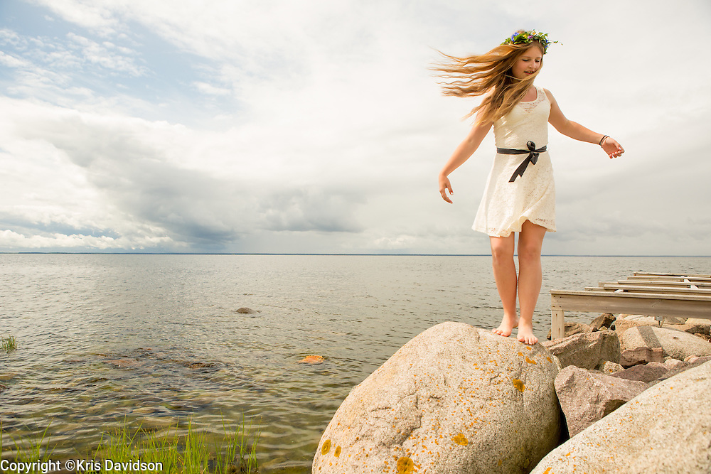 Girl on rock by the Baltic Sea in Öland on midsummer day.