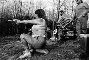 After a bean cook-out with the neighbors, Juli fires a 9mm pistol for target practice at beer cans while Doug Servert and Ray Wolford wait their turn.