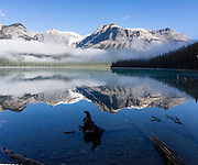 Morning fog breaks to reveal the President Range above Emerald Lake in Yoho National Park, British Columbia, Canada. The Emerald Triangle makes a fine hike of 20 km (12 miles, with 3200 feet gain) around Emerald Lake and over Burgess Pass and Yoho Pass. Yoho is one of several Canadian Rocky Mountains parks which comprise a spectacular World Heritage Area listed by UNESCO in 1984. The panorama was stitched from 2 overlapping images.