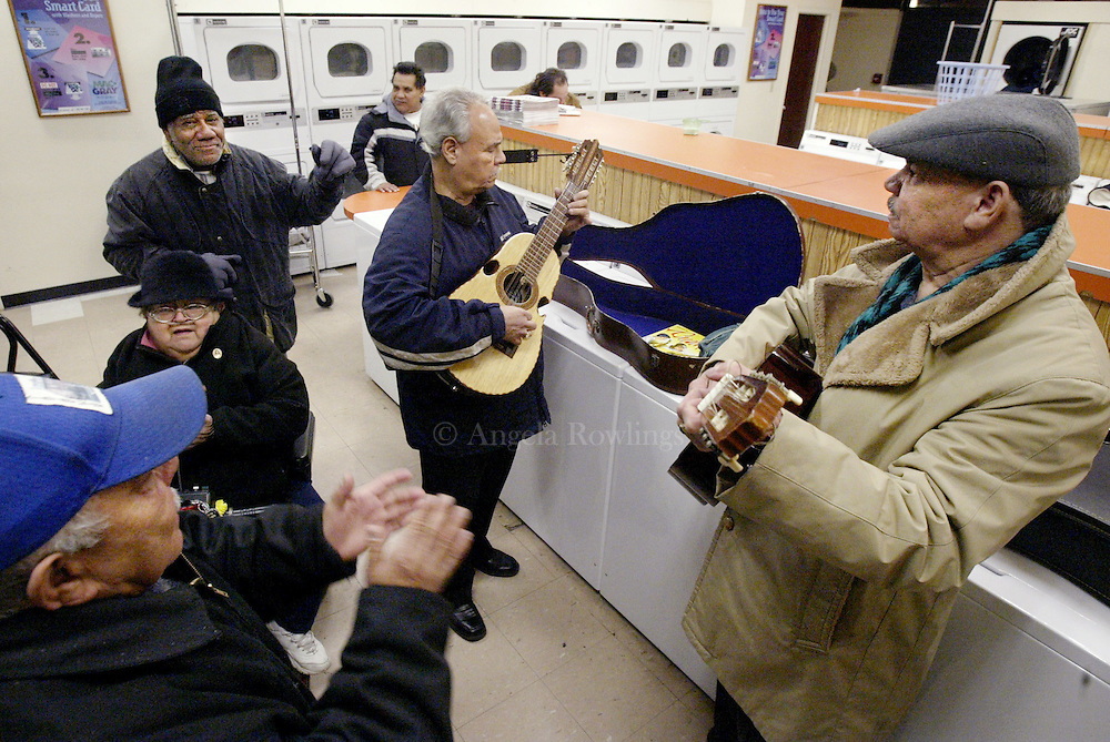 "12/08/05 Boston, MA-- Paco Figueroa, left, claps as Gregorio Nieves plays the cuatro and Pedro Ramos plays the guitar in a laundromat as they begin ""parrandas"" in the Villa Victoria neighborhood of the South End Thursday.  Parrandas are a part of Puerto Rican tradition where Christmas carolers stop at friends and neighbors' houses to sing and party.  (120805parrandasar01, saved in fri, Staff Photo by Angela Rowlings)"