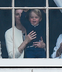 © London News Pictures. 13/06/2015. London, UK.  Prince George of Cambridge being held up by his nanny Maria Borrallo at the window of Buckingham Palace as carriages carrying the royal family leave from Buckingham Palace during the annual Trooping the Colour Ceremony in central London. The event marks the queens official birthday. .Photo credit: Ben Cawthra/LNP