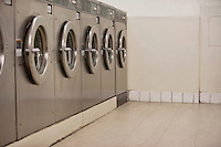 Row of self-service clothes dryers in Laundromat