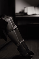 Sensual erotic photograph of sexy young woman in black shoes and stockings sitting in a room with a piano in the background with her beautiful legs tied with a bondage rope