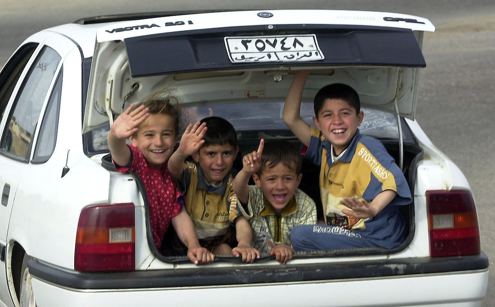 WELCOME.A group of Iraqi children riding in trunk of car wave at a U.S. Army convoy carrying members a U.S. Air Force Global Airfield Assesment Team (GAAT) from McGuire AFB in New Jersey, being escorted by soldiers from the U.S. Army, 173rd Brigade, who gave them added security as they convoyed to an Iraqi military airfield on the outskirts of Kirkuk.
