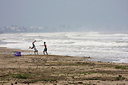 Two young men practicing saltos on China Beach. A typhoon out at sea makes the waves go high.