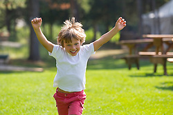 little boy running with his arms up in the air outdoors on a green lawn