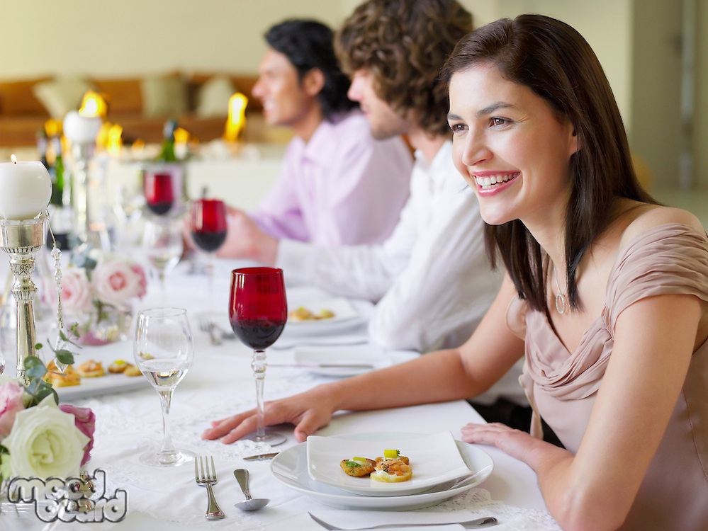 Smiling young woman at dinner party