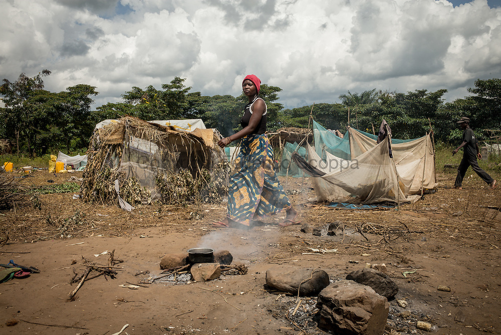 DRC / Burundi Refugees / A woman passes by some improvvised shelters in the Luvungi makeshift camp. Refugees are living in open air spaces cooking on wooden fire and sleeping in small shelter built with mosquito nets. Refugees <br /> More than 9000 Burundians refugees have crossed into the DRC over the past few weeks. The new<br /> arrivals are being hosted by local families, but the growing numbers are straining<br /> available support. Work is ongoing to identify a site<br /> where all the refugees can be moved, and from where they can have access to<br /> facilities such as schools, health centers and with proper security. / UNHCR / F.Scoppa / May 2015