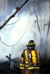 Stock photo of a fire fighter with an oxygen tank working in heavy smoke