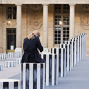 Woman talking on cell phone sits on sculpture column at Palais Royal Paris France<br />