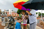 """Annapolis, Maryland - June 05, 2016: A thunderstorm prompts siblings Maia, 8, middle, and Adham Eissa, 9, background, and their friend Christopher, left, (parents don't want his last name published) to huddle under their parents umbrella at the Kunta Kinte-Alex Haley Memorial statue in historic Annapolis Sunday June 5th, 2016. Earlier that day a perigean spring tide brought some of the highest water levels of the year to the coastal town and partially flooded the park. Thunderstorms are a more common cause of nuisance flooding in Annapolis. <br /> <br /> A perigean spring tide brings nuisance flooding to Annapolis, Md. These phenomena -- colloquially know as a """"King Tides"""" -- happen three to four times a year and create the highest tides for coastal areas, except when storms aren't a factor. Annapolis is extremely susceptible to nuisance flooding anyway, but the amount of nuisance flooding has skyrocketed in the last ten years. Scientists point to climate change for this uptick. <br /> <br /> <br /> CREDIT: Matt Roth for The New York Times<br /> Assignment ID: 30191272A"""