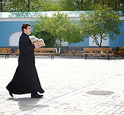 Kiev, Ukraine <br /> people and places, churches and street art around Kiev city centre which hosts the Eurovision Song Contest on 13th May 2017 at the International Exhibition Centre in Kiev, Ukraine<br /> A priest at St Michael's Golden Domed Monestery carries books between buildings <br /> Kiev in Ukraine <br /> <br /> Photograph by Elliott Franks <br /> Image licensed to Elliott Franks Photography Services