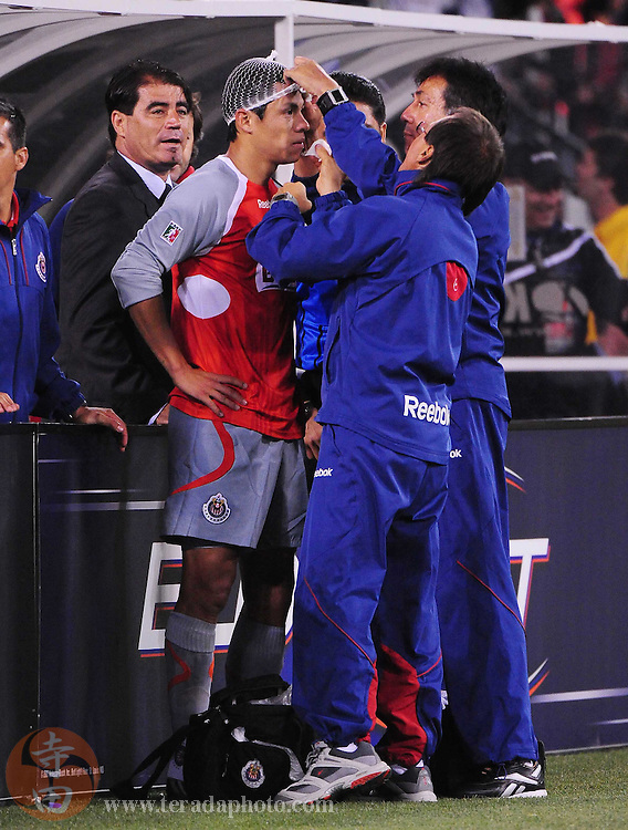 August 8, 2009; San Francisco, CA, USA; Chivas de Guadalajara midfielder Gonzalo Pineda (center) receives medical attention as head coach Francisco Ramirez (left) looks on during the first half against FC Barcelona in the Night of Champions international friendly contest at Candlestick Park.