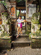 11 OCTOBER 2016 - UBUD, BALI, INDONESIA: A woman leaves the Hindu temple in the market in Ubud. The temple in the market is very busy during the midmorning hours, when market vendors come to pray. The morning market in Ubud is for produce and meat and serves local people from about 4:30 AM until about 7:30 AM. As the morning progresses the local vendors pack up and leave and vendors selling tourist curios move in. By about 8:30 AM the market is mostly a tourist market selling curios to tourists. Ubud is Bali's art and cultural center.      PHOTO BY JACK KURTZ