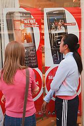 Teenage girls looking at mobile phone advert.