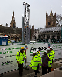 © Licensed to London News Pictures. 09/02/2016. London, UK. Members of Greenpeace have installed a 10 meter life-lke fracking rig and drill outside the houses of parliament on Parliament Square in London. The rig emits a flame created using bio ethanol. The protest coincides with the first day of the independent Planning Inspectorate inquiry into whether fracking will go ahead in Lancashire.Photo credit: Peter Macdiarmid/LNP