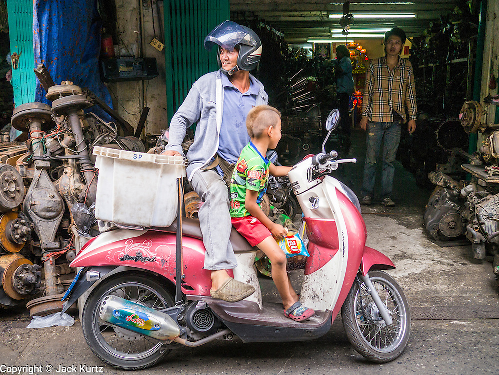 20 APRIL 2013 - BANGKOK, THAILAND:   A boy and his father on their motor scooter in Talat Noi (Talat means Market, Noi means Small. Literally Small Market). The Talat Noi neighborhood in Bangkok started as a blacksmith's quarter. As cars and buses replaced horse and buggy, the blacksmiths became mechanics and now the area is lined with car mechanics' shops. It is one the last neighborhoods in Bangkok that still has some original shophouses and pre World War II architecture. It is also home to a  Teo Chew Chinese emigrant community.   PHOTO BY JACK KURTZ