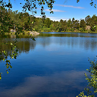 2nd Stampe Lake at Baneheia Park in Kristiansand, Norway <br /> Northeast of town is a lovely park named Baneheia. To reach it, you must hike up one of two steep trails. But the trek is worth it once you discover the tree-lined lakes called 1st, 2nd and 3rd Stampe. They were formed by old stone dams once used to supply the town with water. Now they offer the locals an all-season recreational area including about 1.3 miles of hiking paths. They are also popular swimming holes during the summer. Tourists especially enjoy the wonderful views of the city below. Another nearby park to explore is Ravnedalen or Raven's Valley.